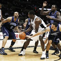 San Antonio Spurs player George Hill, center, looks to pass around Utah Jazz forward Carlos Boozer to teammate Tim Duncan, left, as the Jazz's Deron Williams, right, and Paul Millsap try to strip the ball during the second half.