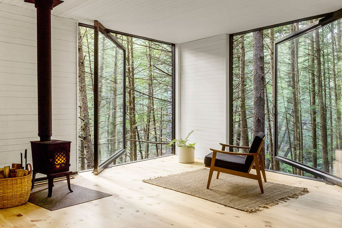 Interior of white-walled cabin with two large floor-to-ceiling picture windows that pivot out and frame views of the wooded site.