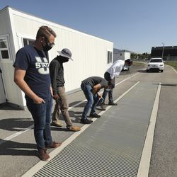 Students and professors look over a solar-powered track equipped with power transfer coils embedded in the roadway, enabling properly equipped electric vehicles to charge while they're in motion, at Utah State University's Engineering Research Center for Electrified Transportation in North Logan on Thursday, Aug. 6, 2020. USU will be the lead institution for a five-year, $26 million grant to develop an international research center dedicated to advancing sustainable, electrified transportation.