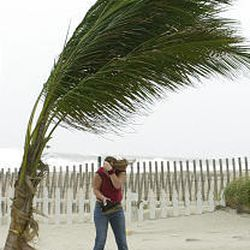 Melanie Krogh of Norfolk, Va., leans against the blowing sand from winds whipped up by Hurricane Isabel on the beach in Sea Bright, N.J., on Thursday.