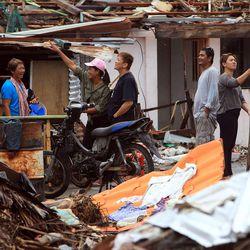 Neighbors talk in the street near their homes in Tacloban, Friday, Nov. 22, 2013.