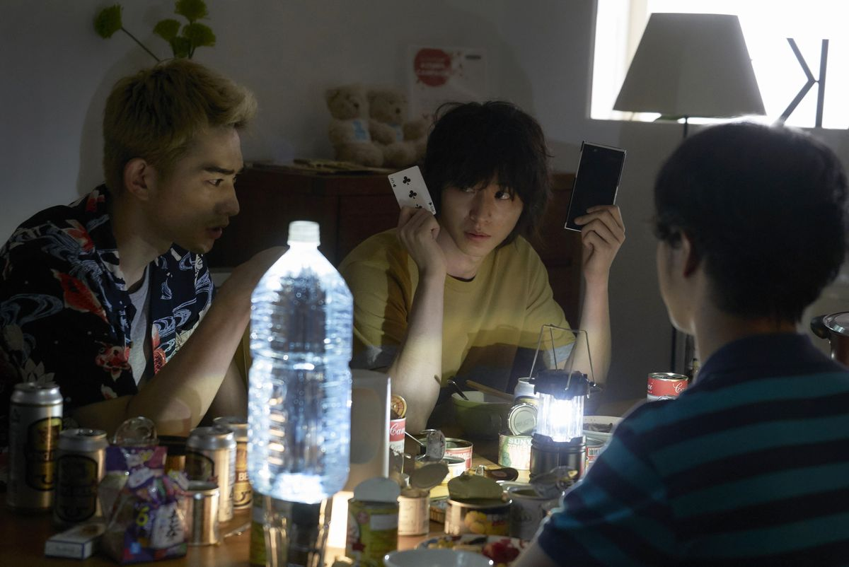 Ryōhei Arisu (Kento Yamazaki) holding a playing card and a cell phone in his hands at a dinner table in Alice in Borderland.