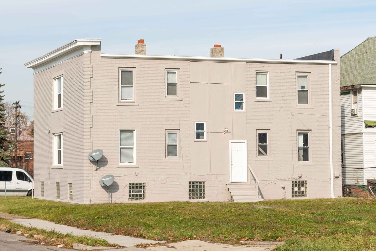 Back of the plain white building. There's two windows for each unit on the upper and lower floor.