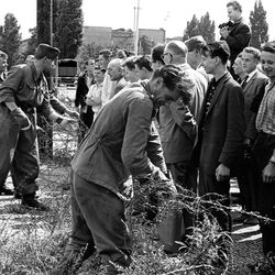 East German soldiers, left, set up barbed wire barricades August , 13, 1961 at the border seperating Berlin, Germany, to restrict the travel between the eastern and western part of the German city. West Berlin citizens, right, watch the work.