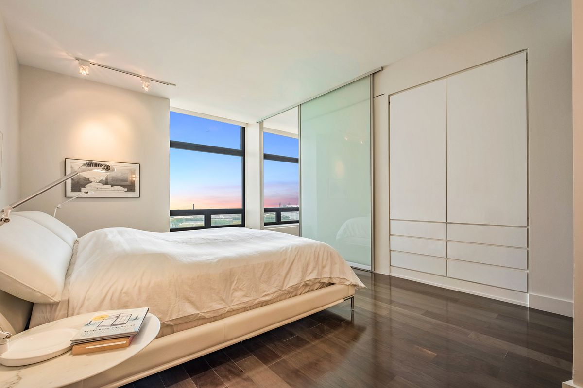 One of the three bedrooms, this features a built-in closet, a sliding glass door, and lake views.