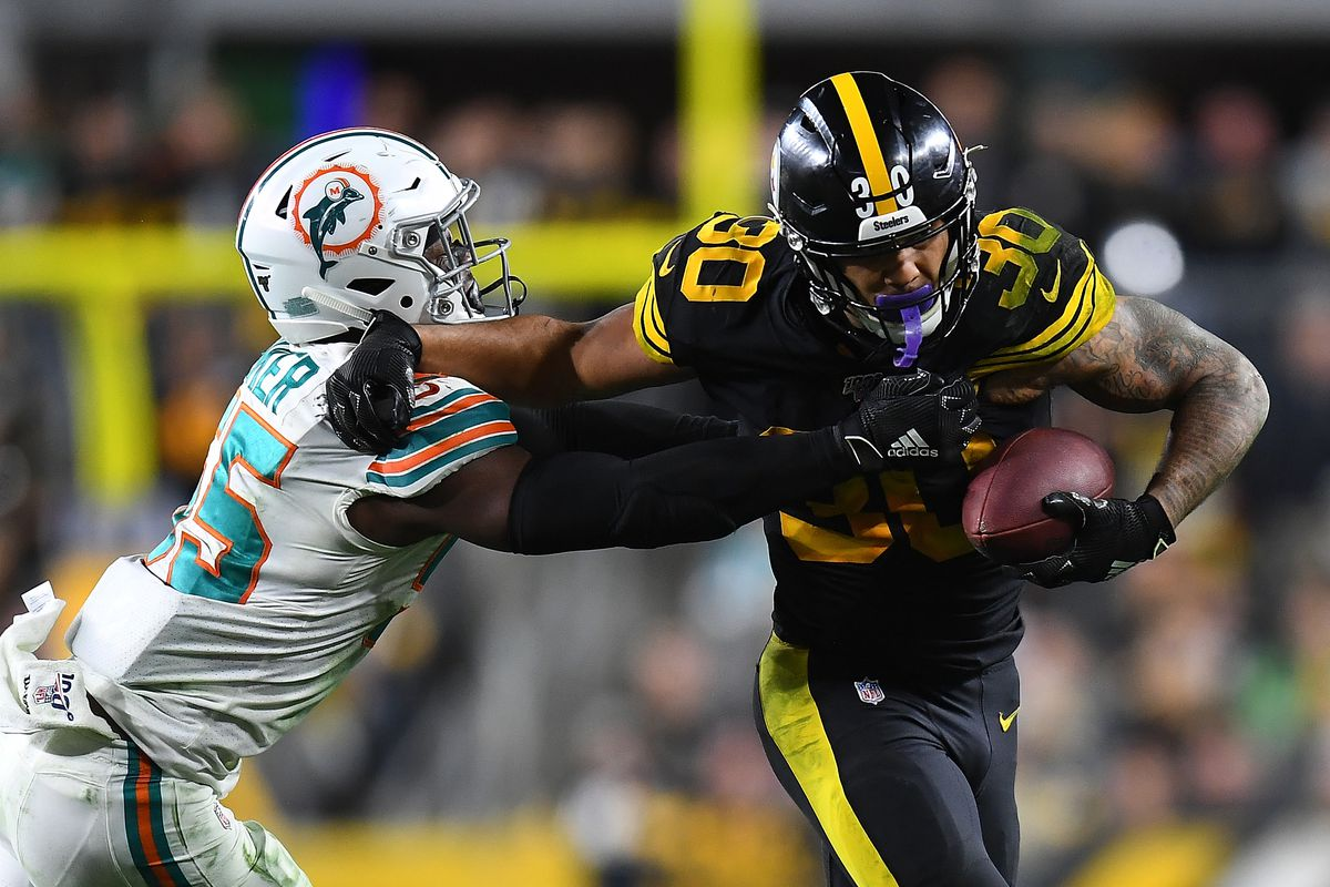 James Conner of the Pittsburgh Steelers is wrapped up by Jerome Baker of the Miami Dolphins during the fourth quarter at Heinz Field on October 28, 2019 in Pittsburgh, Pennsylvania.