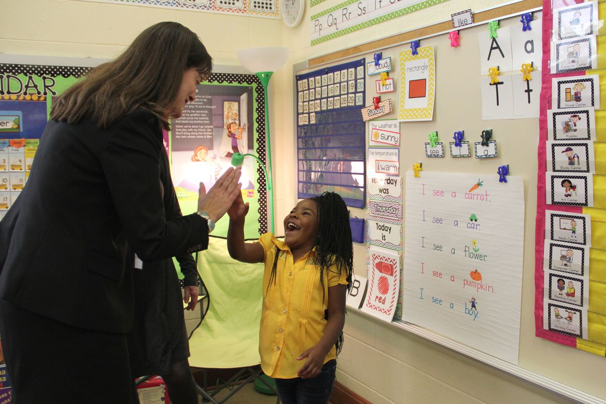 Education Commissioner Candice McQueen congratulates a student at Springdale Memphis Magnet School during a September visit to acknowledge the school's improved academic scores.