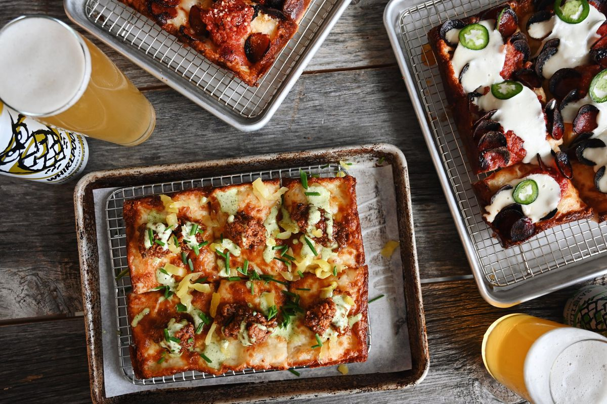 Overhead view of three different Detroit-style pizzas and a couple glasses of beer