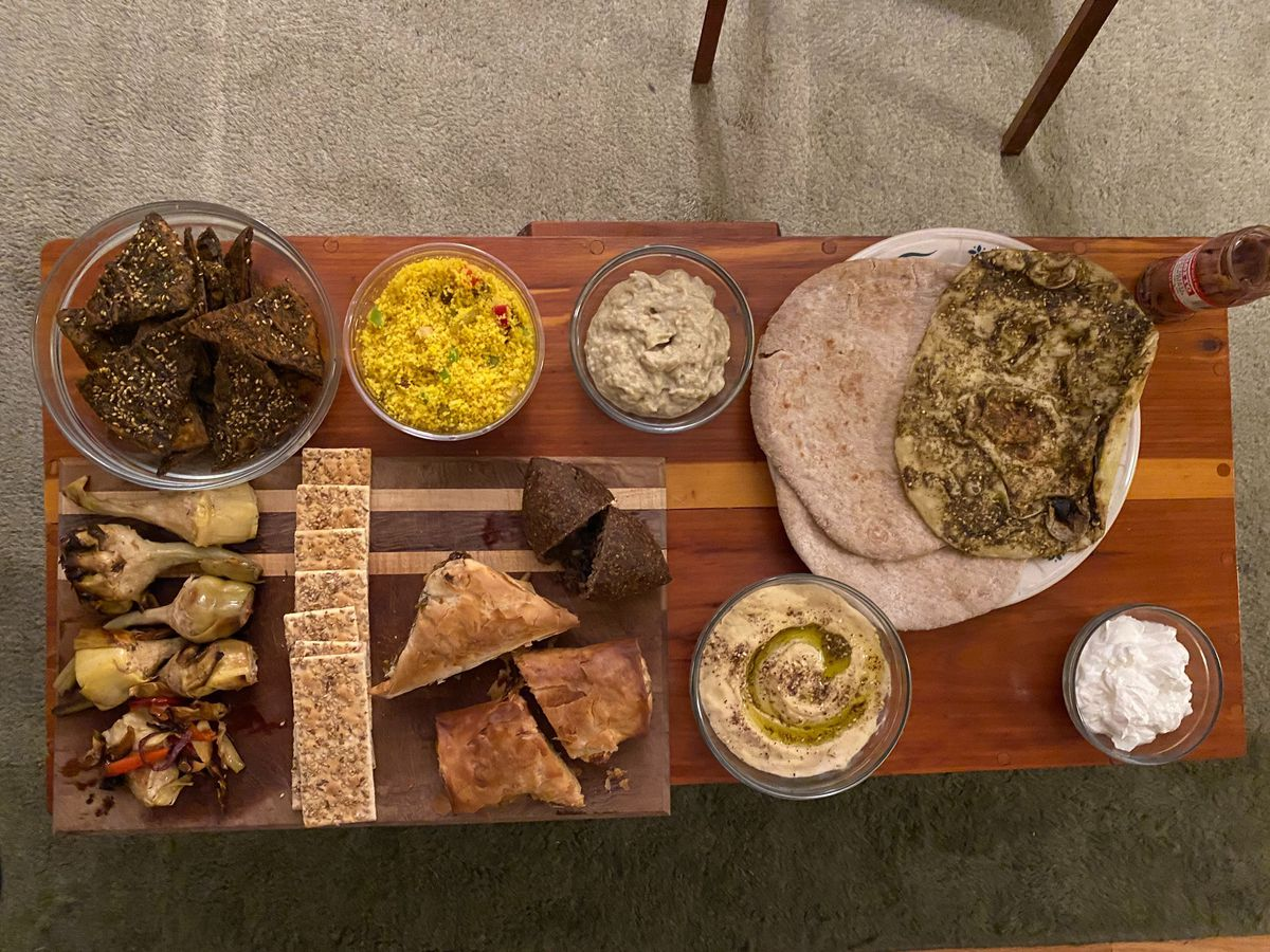 A spread of dips, chips, pita breads, filo pies, and grilled vegetables laid out on a wooden table
