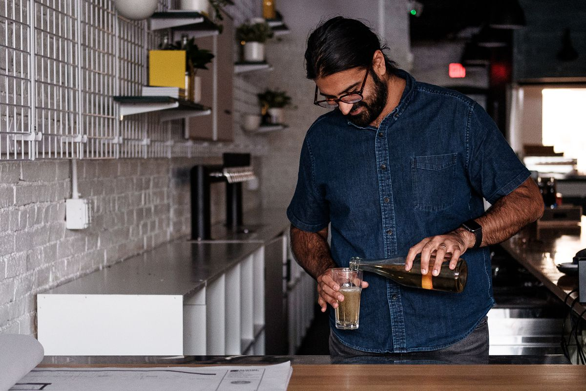 A man with dark hair, a beard, and glasses pours hard cider from a bottle into a glass. He is wearing a short-sleeved blue denim collared shirt and standing at a bar in a dimly lit taproom.