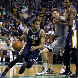 Utah Jazz guard Trey Burke (3) drives to the basket as Boston Celtics forward Jonas Jerebko (8) is picked by Jazz forward Trevor Booker, right, during the first half of an NBA basketball game in Boston, Wednesday, March 4, 2015. (AP Photo/Elise Amendola)