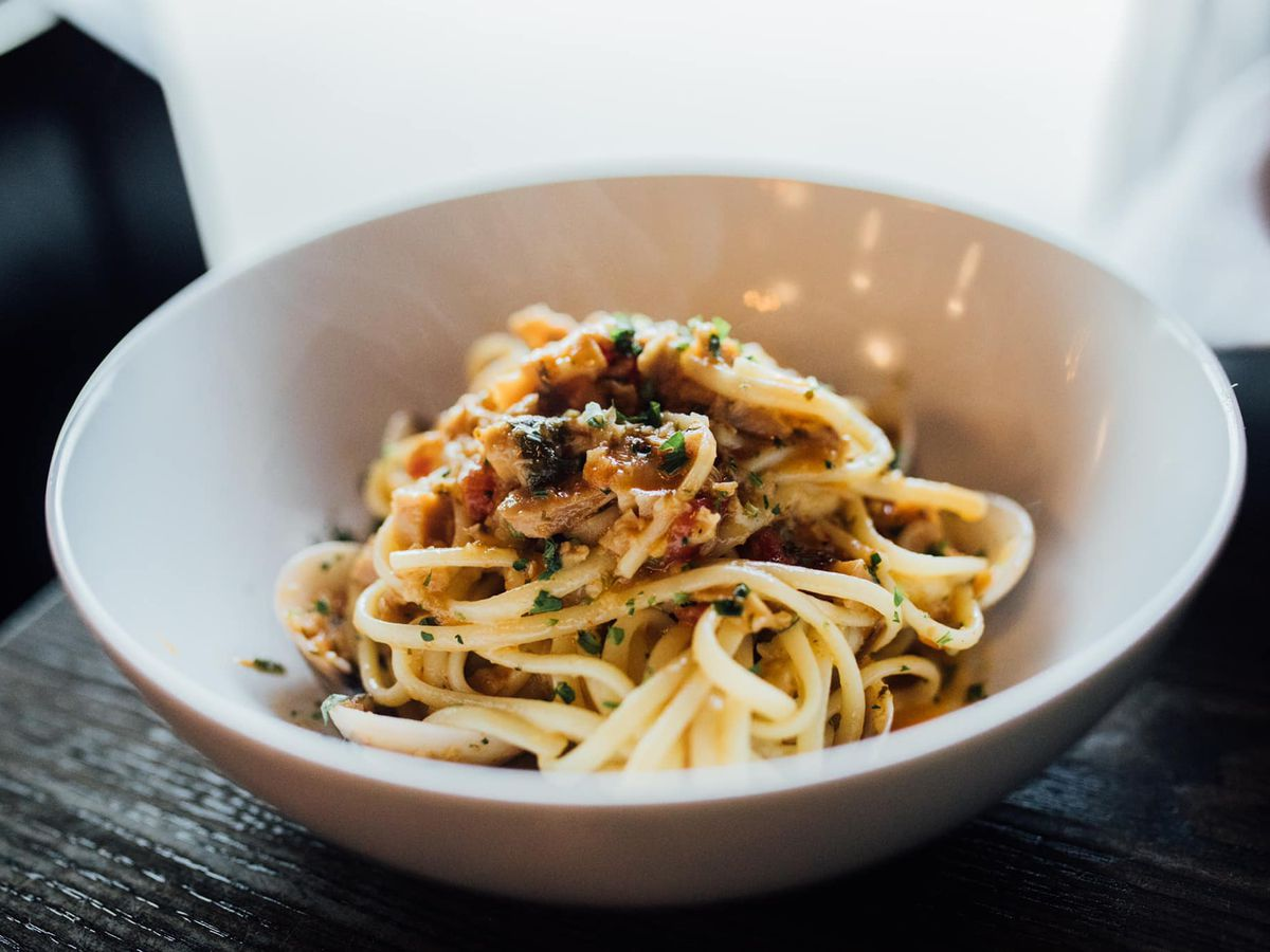 A bowl of pasta with toppings on a dark wood table
