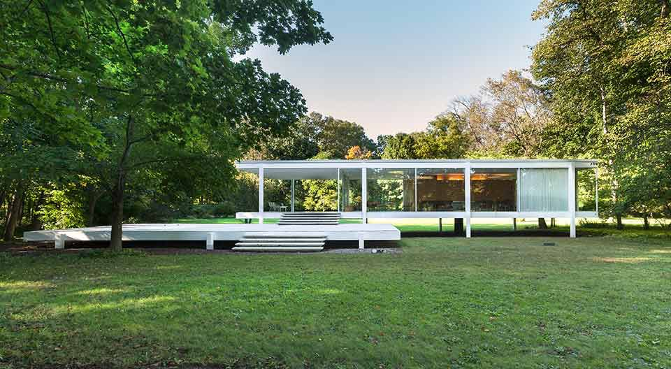 The exterior of the Farnsworth House in Illinois. The house is one level with a flat roof and floor to ceiling windows. There is a lawn and trees surrounding the house.