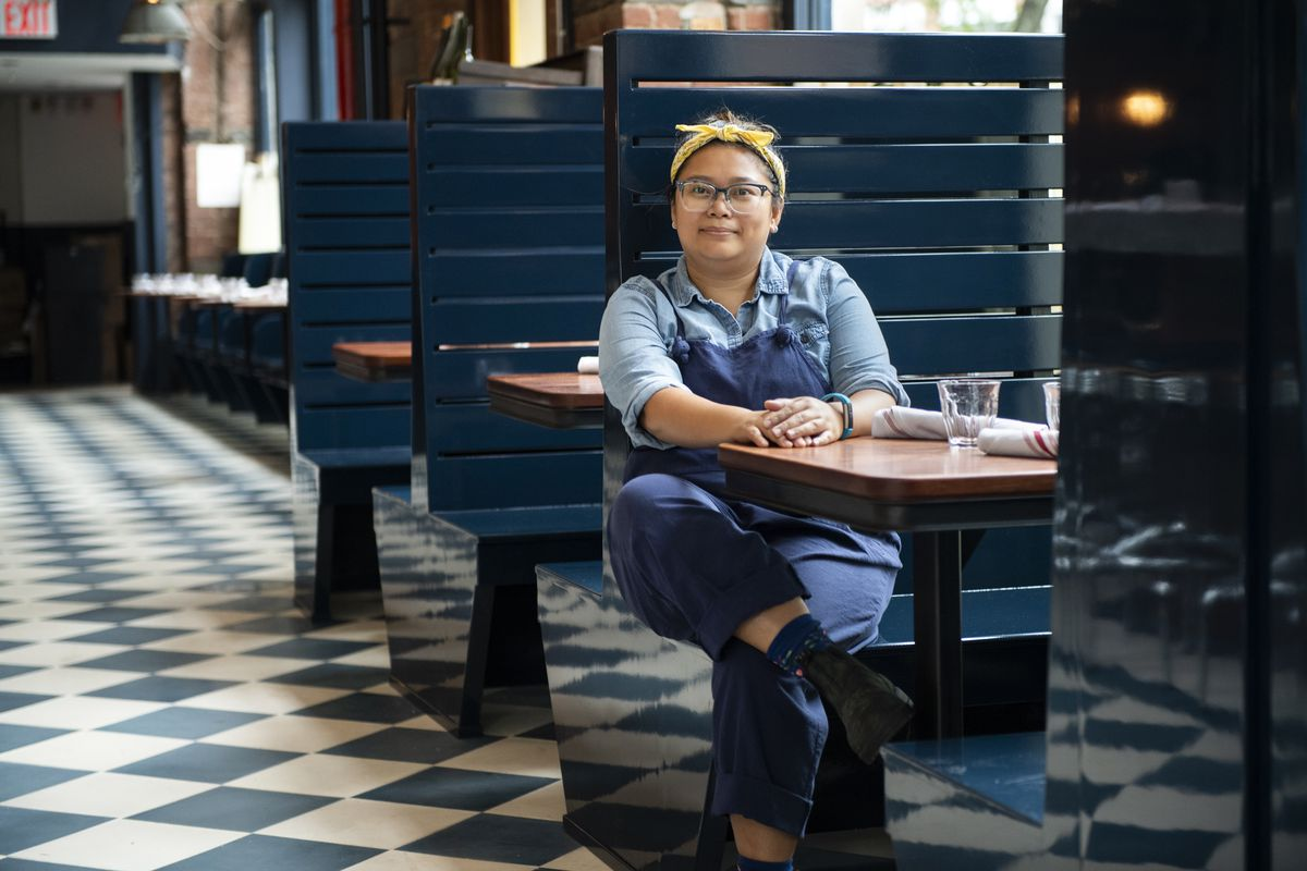 Charlene Santiago sitting in a blue booth inside a restaurant with checkered floors