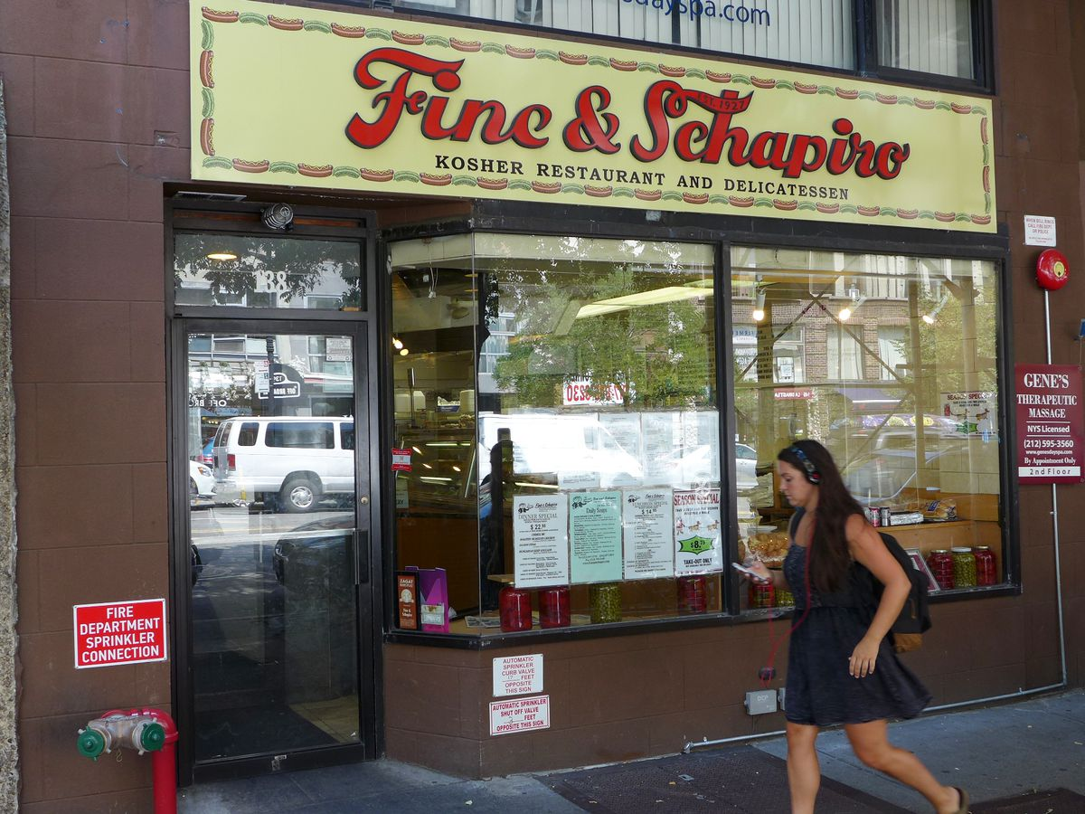 """A woman walks by the front of a windowed storefront, whose yellow and red sign reads: Fine & Schapiro: Kosher Restaurant and Delicatessen"""""""