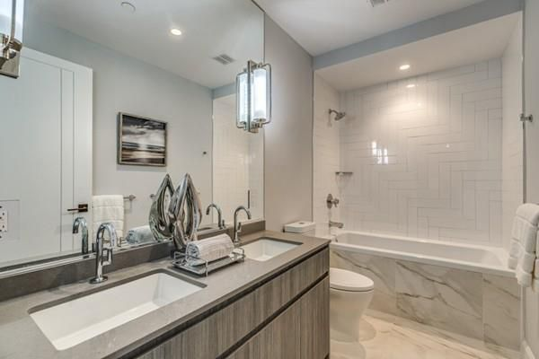 A bathroom with a double-sink vanity and a shower with no curtain.