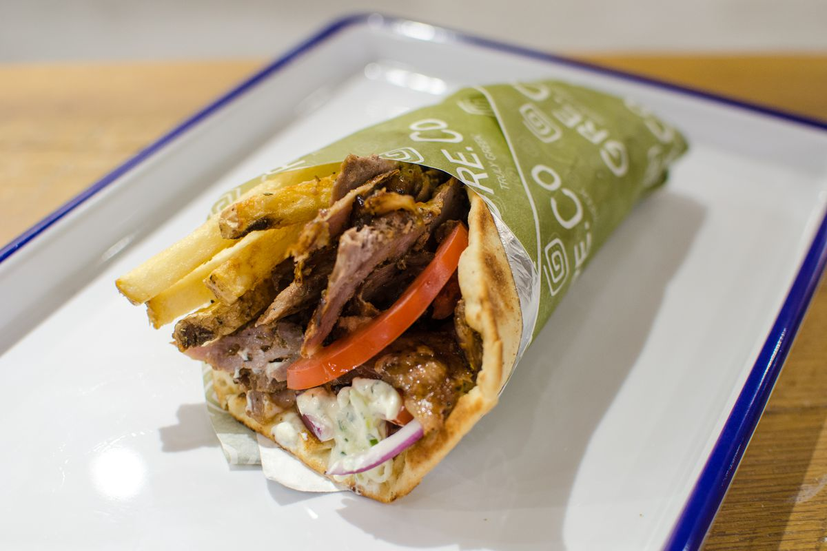 A meat gyro stuffed with fries, red onion, and tzatziki is wrapped in green paper and sits on a white tray on a wooden table.