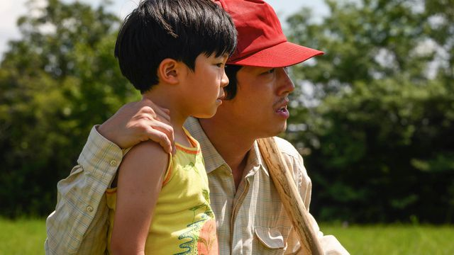 steven yeun in a red cap stands with a young boy in a field