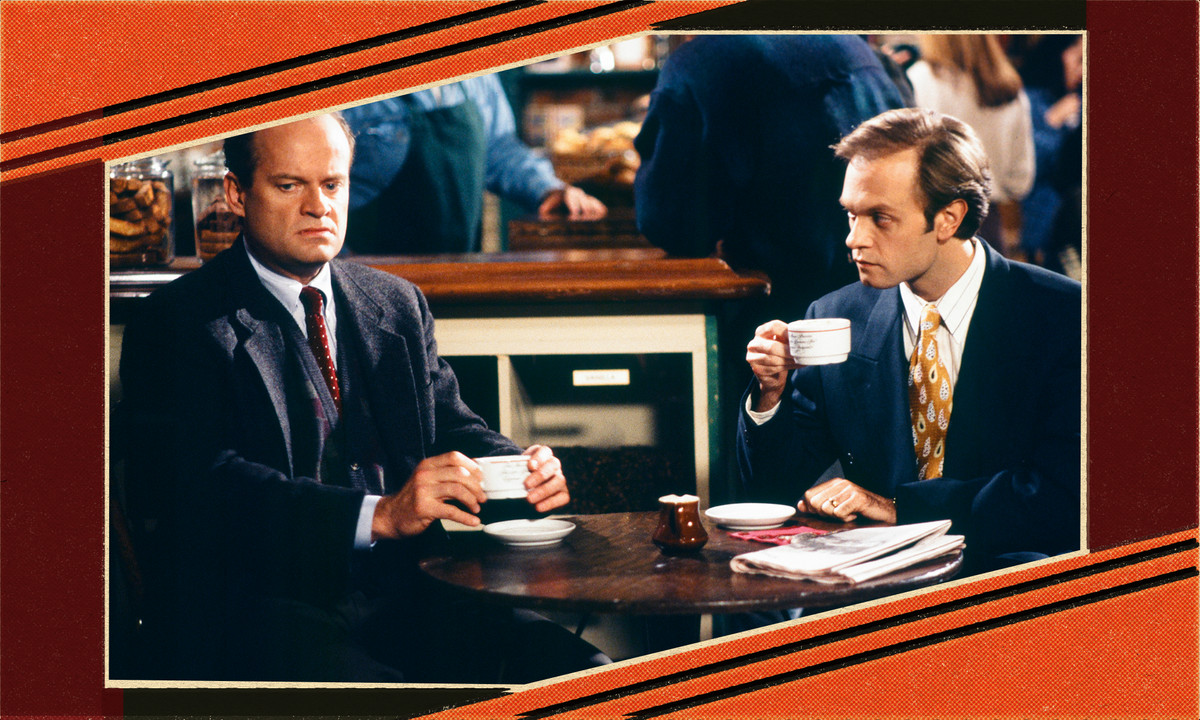 Two men in suits sit at a table with white cups.