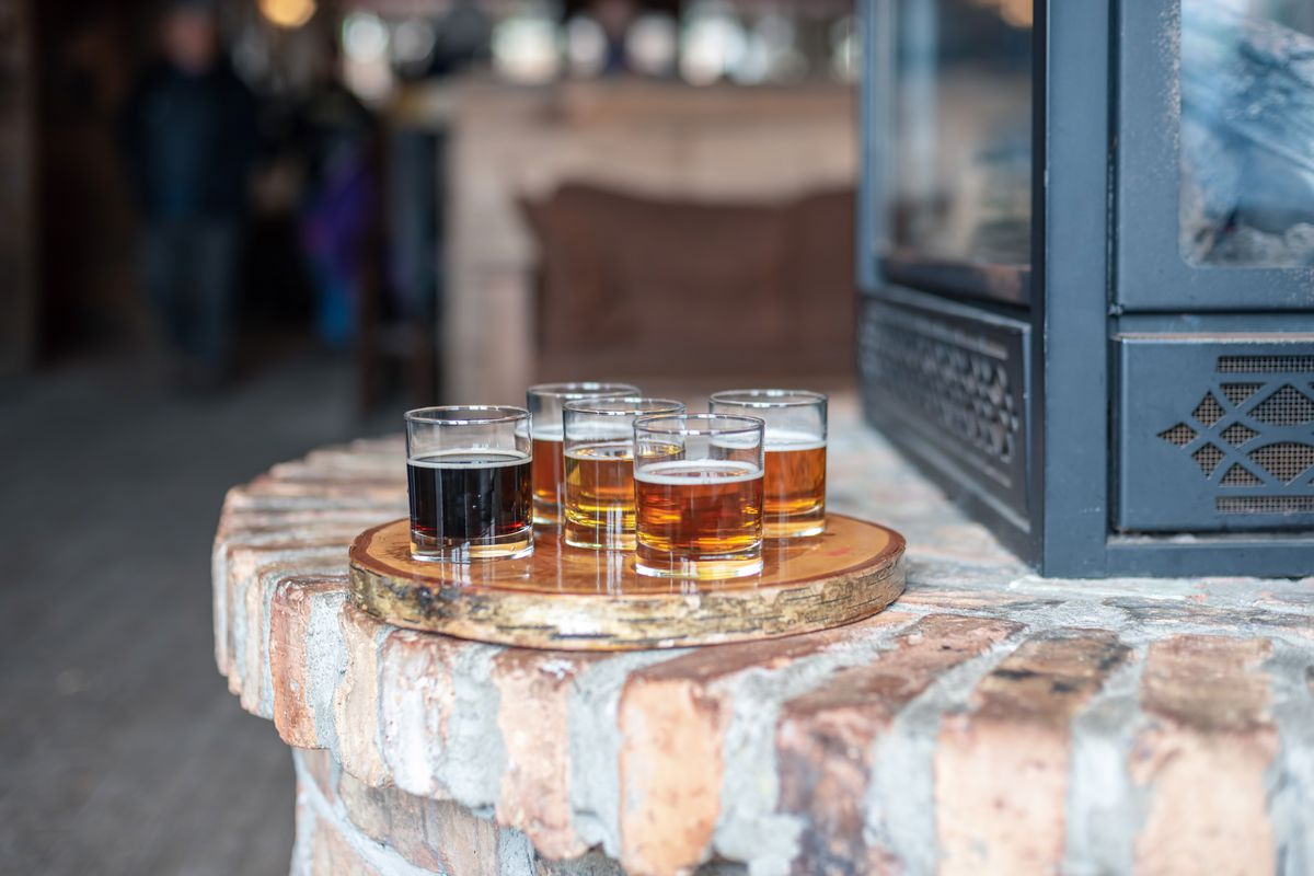 Tasting glasses of beer on rustic serving tray by the fire at local microbrewery.