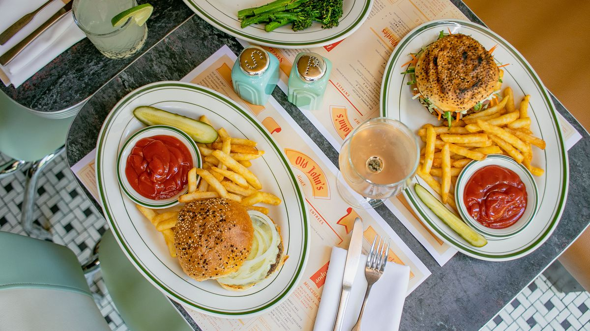 An overhead shot of oval dishes with burgers, french fries, pickles, and greens laid out across two blue tables with booths and chairs on the side