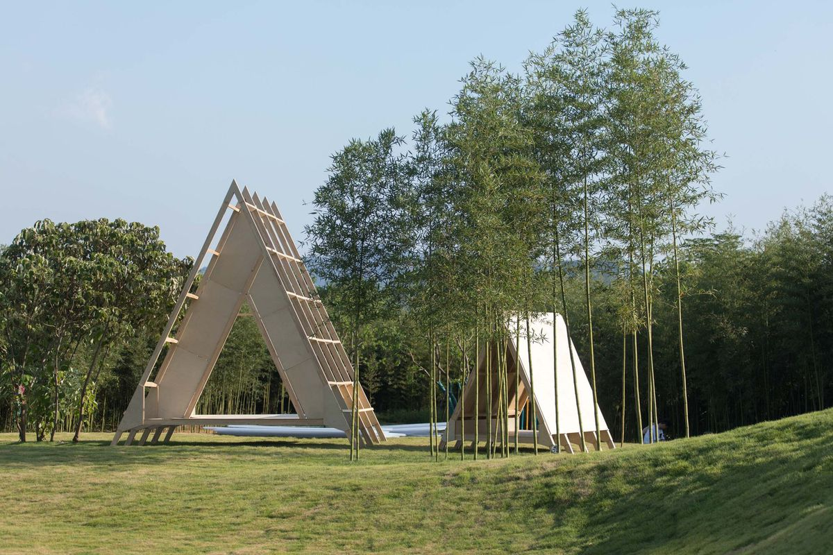 Wooden A-frame buildings on grassy land.