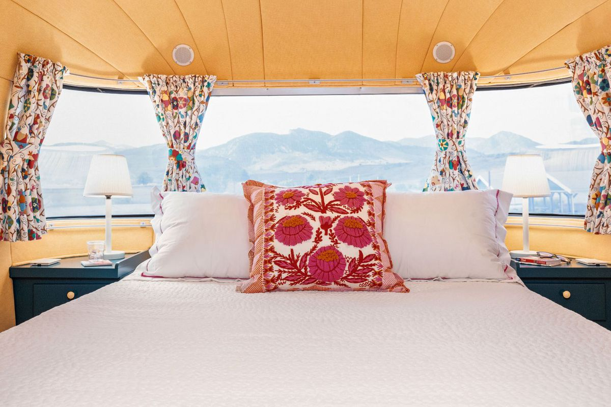 The bedroom of the travel trailer features a white bed with red floral pillow, yellow ceilings, and a panoramic window that shows the mountains outside.