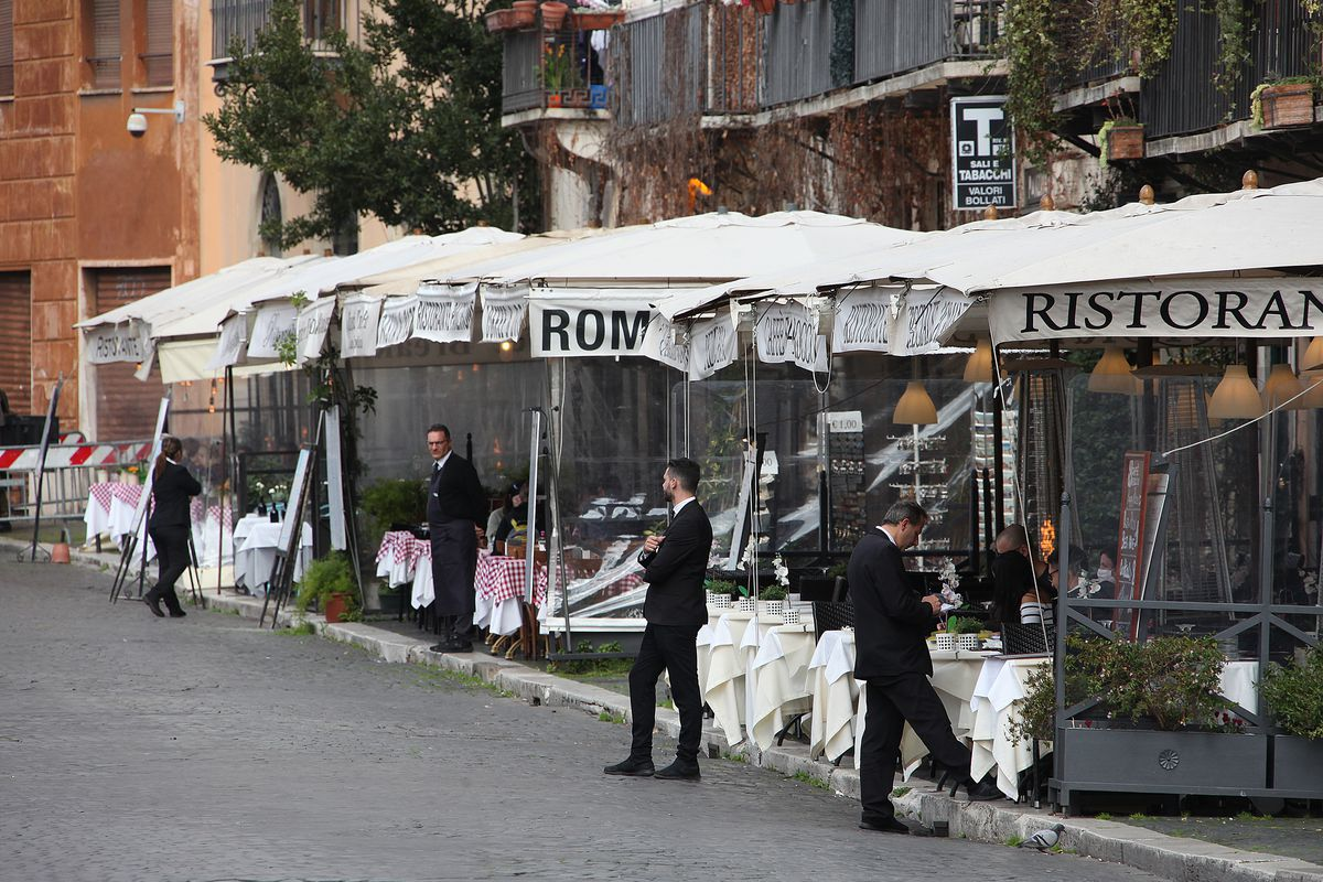 Waiters in tuxes linger on a street in Rome with empty restaurant patios behind them.