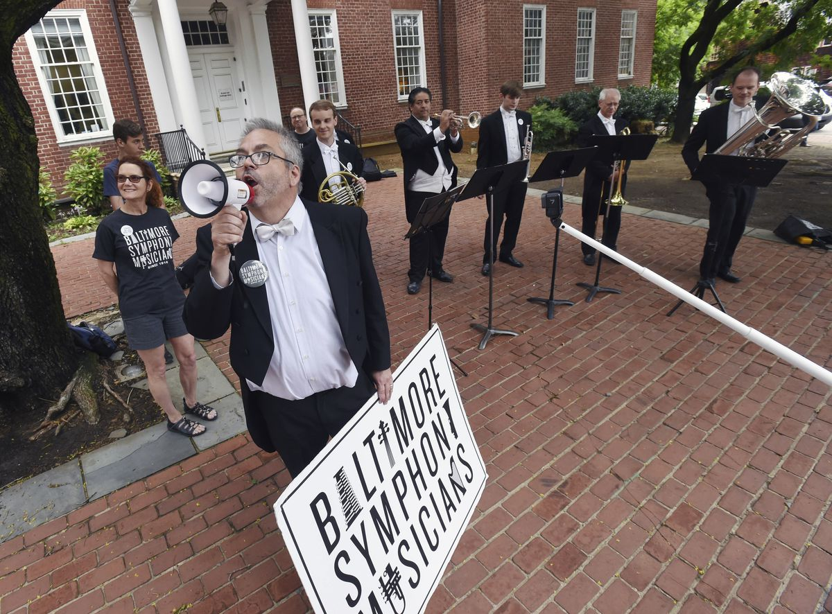In this June 13, 2019 photo, Baltimore Symphony Orchestra oboist Michael Lisicky, second left, conveys a message to Gov. Hogan as fellow members of the brass section play music as they protest at the State House in Annapolis, Maryland. The BSO's players h
