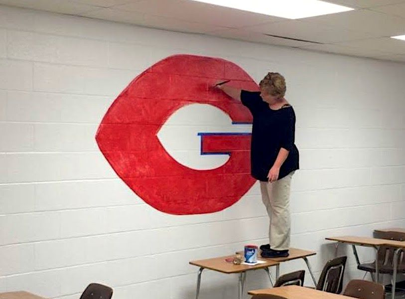 Camille Collins, who has spent her entire 25-year teaching career at Germantown High School, paints the school logo on her classroom wall.