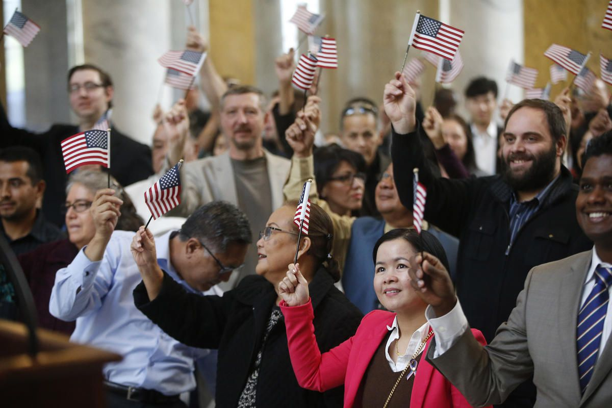 U.S. flags are waved during a United States Citizenship and Immigration Services naturalization ceremony in the Capitol rotunda in Salt Lake City on Monday, Sept. 25, 2017.