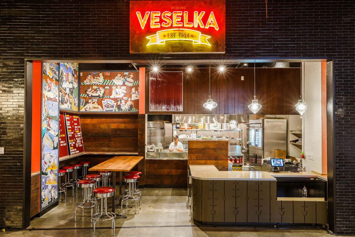 """A red and yellow neon sign says """"Veselka"""" above a small counter and restaurant."""