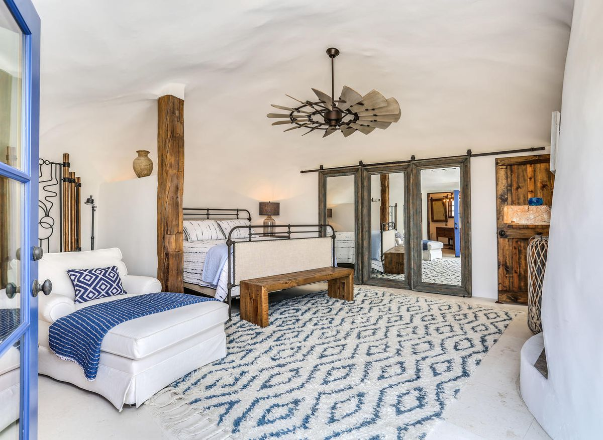 A blue and white bedroom has a white bed, white arm chair, blue and white rug, and large fan.