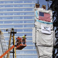 """Construction workers watch as an original piece of the Twin Towers, known as a """"trident,"""" is lowered into its permanent location at the 9/11 Memorial Museum at ground zero in New York, Tuesday, Sept. 7, 2010."""