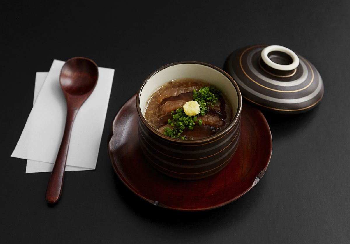 A brown bowl that holds a brown soup-like dish with some chopped greens on top. A wooden spoon is adjacent to the bowl