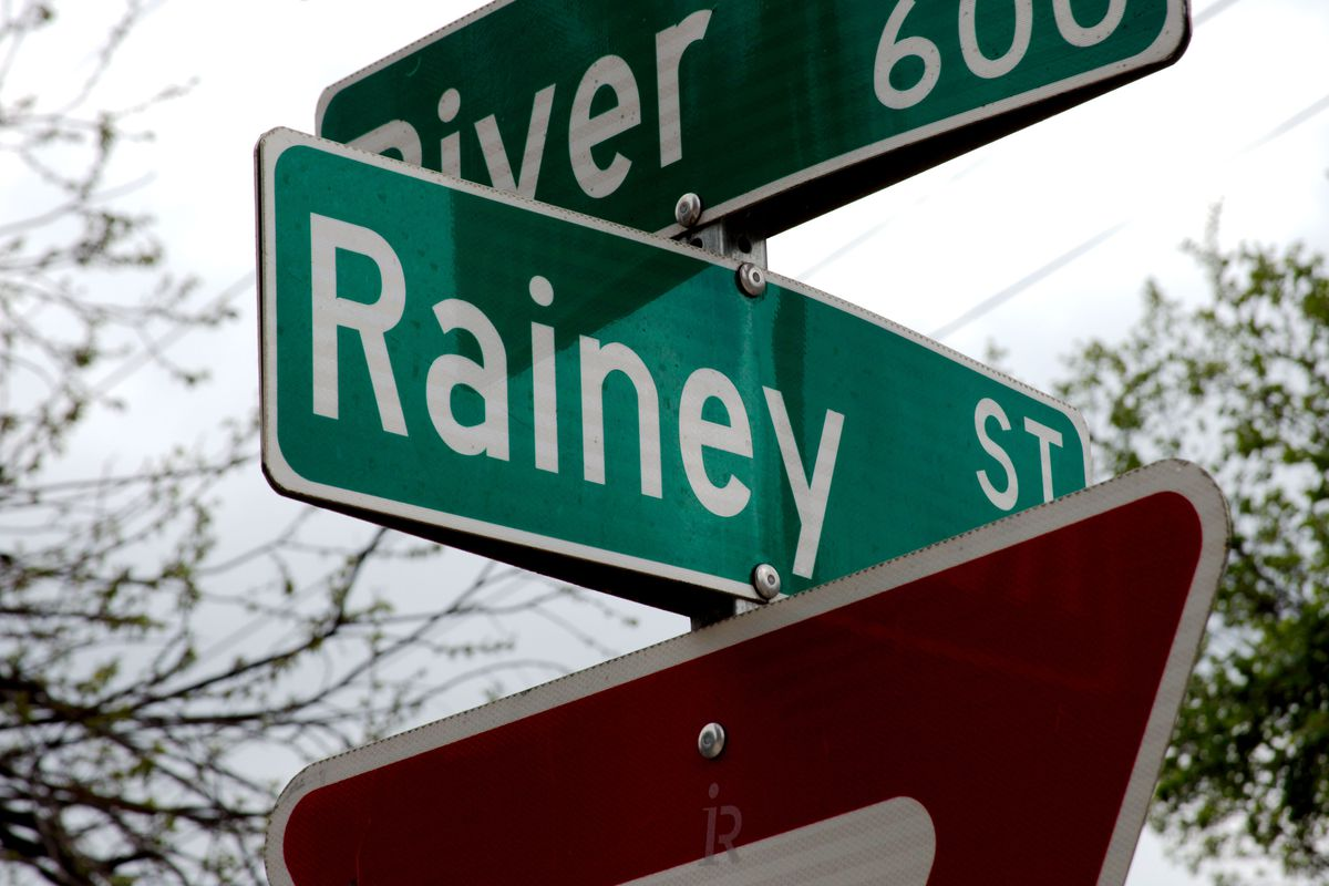 """Green street signs with white lettering that read """"River"""" on the top one and """"Rainey"""" on the bottom one. They are crossed on top of a post with part of a red and white triangular """"Yield"""" underneath."""