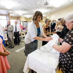 Gigi Turley waits her turn as Cristi Fitzgerald has her hands dried by Jeri Lambourne as they gather for the World Spiritual Health Organization combined board certification and chaplain graduation ceremony at the William E. Christofferson, Salt Lake Veterans Home on Wednesday, Aug. 2, 2017.