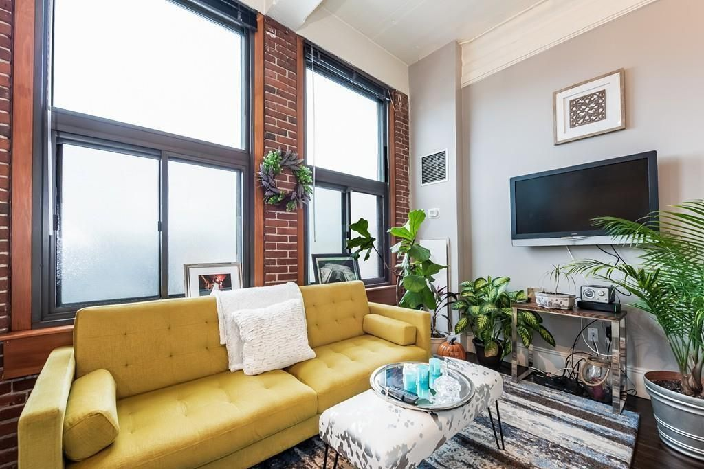 The living room with its large windows and a couch, and there's a TV mounted on the wall.