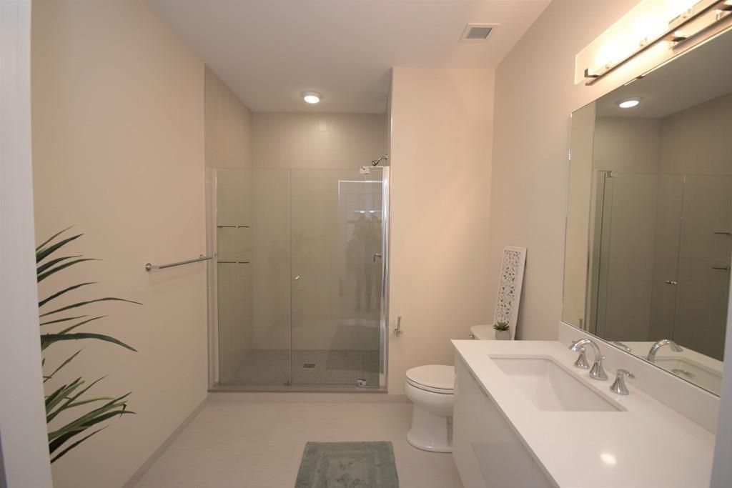 A modern bathroom ending in a glass-enclosed shower.
