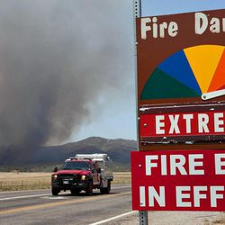 A fire engine moves along Hays Ranch Road as the Yarnell Hill Fire advances on Peeples Valley, Ariz. on Sunday, June 30, 2013. The fire started Friday and picked up momentum as the area experienced high temperatures, low humidity and windy conditions. It has forced the evacuation of residents in the Peeples Valley area and in the town of Yarnell. (AP Photo/The Arizona Republic, Tom Story)