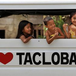 Children smile from the back of a truck in Tacloban, Friday, Nov. 22, 2013.