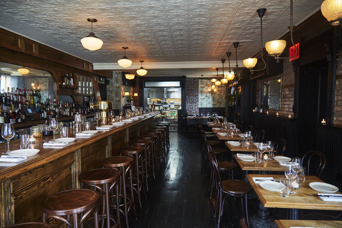 The interior of red hook tavern with a low white paneled ceiling, wooden chairs and tables throughout