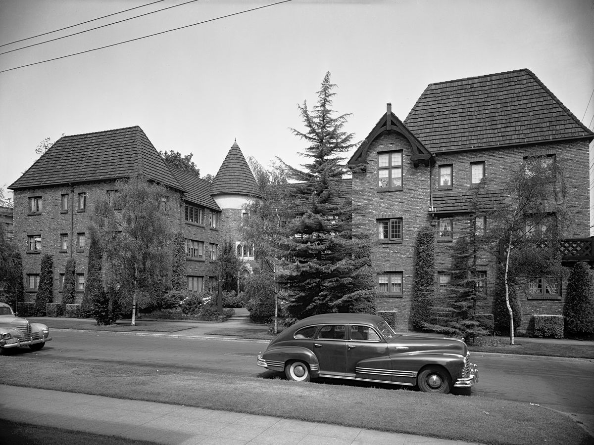 A black-and-white photograph of an elaborate, brick building with two wings wrapping around a central courtyard, with a turret to the left. A 1940s car is on the street in front.