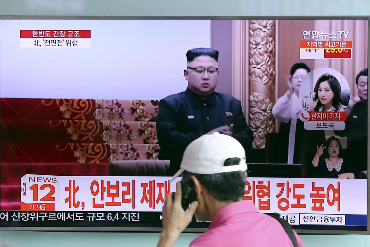 """A man walks by a TV screen showing a local news program with a file image of North Korean leader Kim Jong Un, at Seoul Train Station in Seoul, South Korea, Wednesday, Aug. 9, 2017. The letters read """" North Korea, Denouncing the U.N. Security Council's san"""