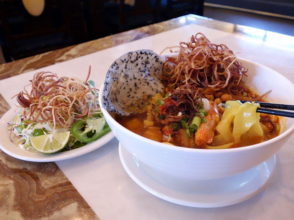A bowl of mi quang, with turmeric noodles, pork spare ribs, prawns, and quail eggs.