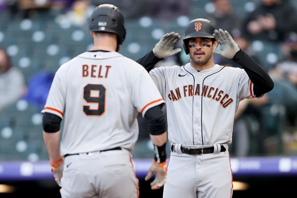Brandon Belt #9 of the San Francisco Giants is congratulated after crossing home plate by Mike Tauchman #29 after hitting a 2 RBI home run against the Colorado Rockies in the first inning during game two of a double header at Coors Field on May 04, 2021 in Denver, Colorado.