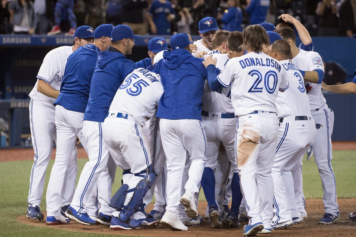 The Jays mob Justin Smoak at home plate following his dramatic walk-off HR in the 10th