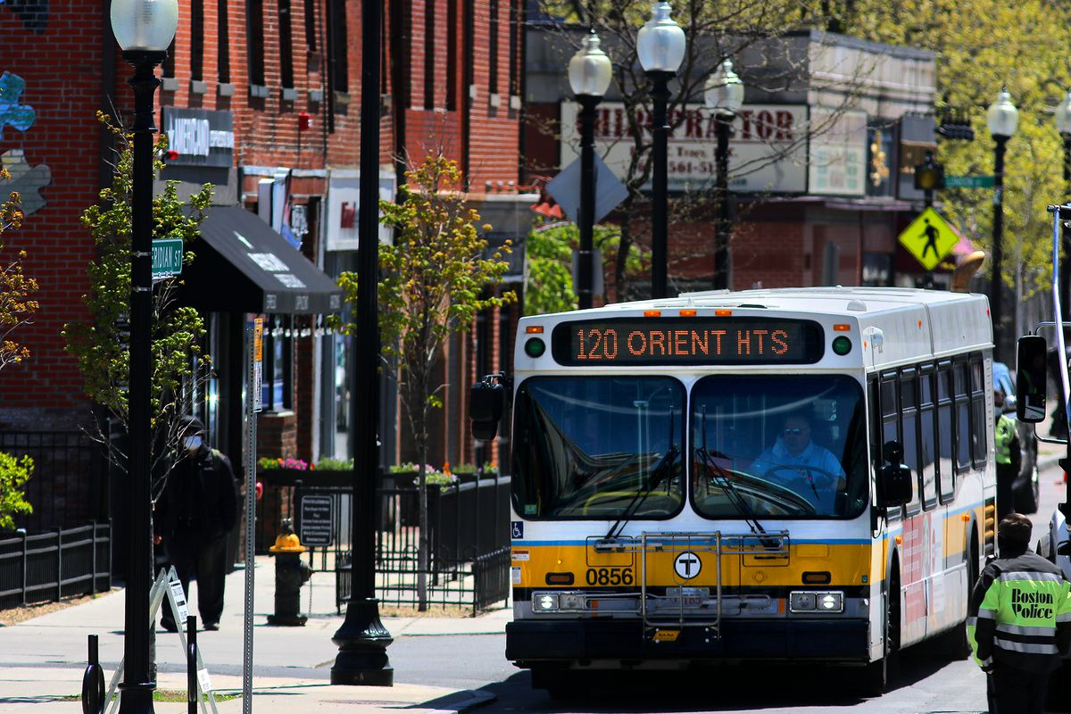 A yellow and blue striped bus with a heading that reads 120 Orient Heights travels along Meridian Street in East Boston, a busy street lined with brick buildings.