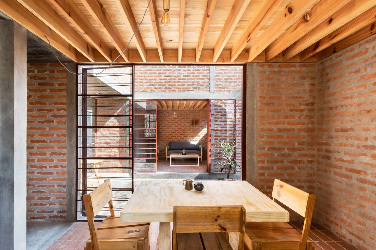Dining area with wooden table looking out onto courtyard.
