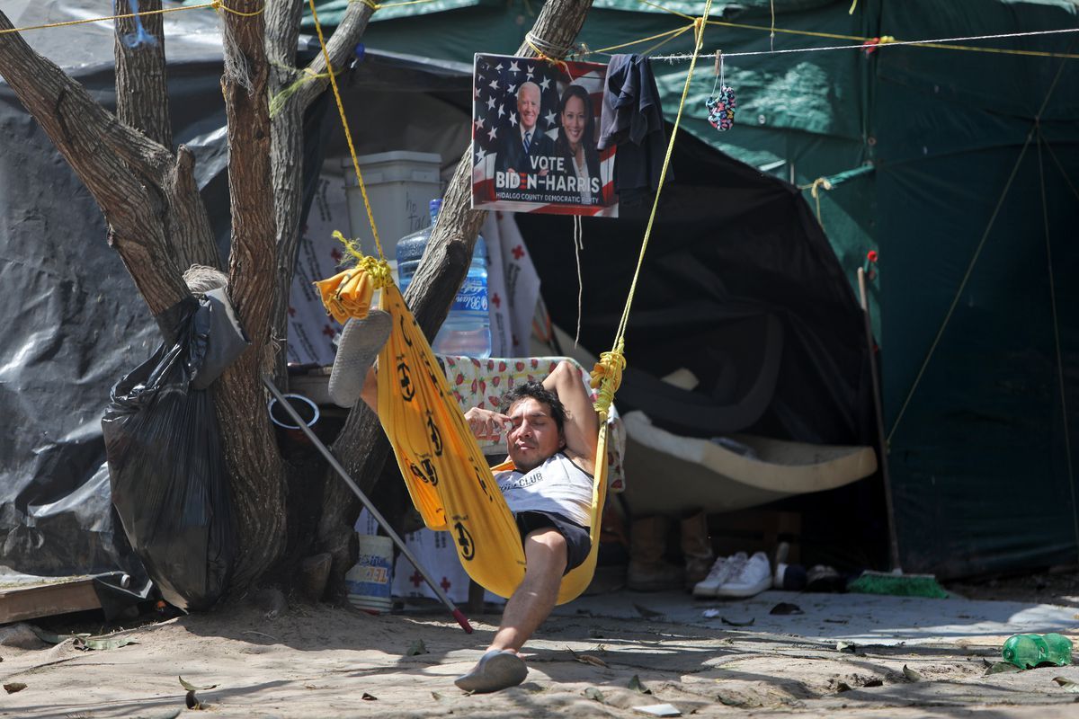 """A Honduran migrant relaxes in a hammock under a """"Vote Biden-Harris"""" sign in the migrant camp in Matamoros, Tamaulipas, Mexico, on Tuesday, Feb. 23, 2021."""